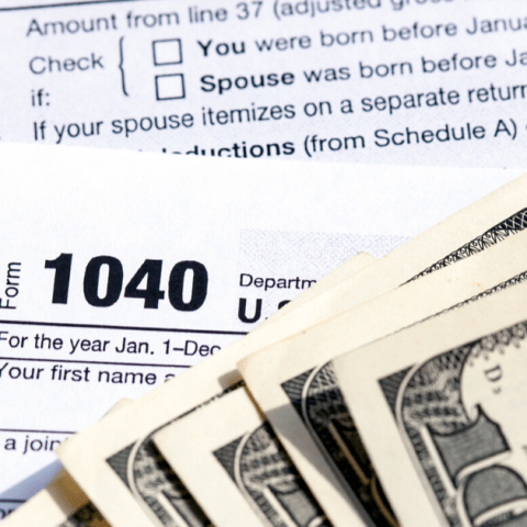 USA 1040 Individual Income Tax Return Form with one hundred dollar bills.
