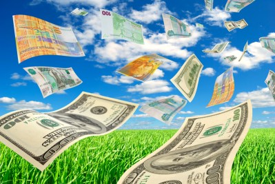 The deformed banknotes of different countries against the blue sky