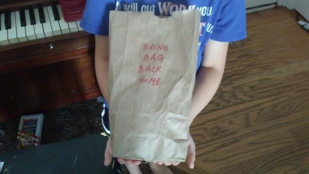 child holding paper bag
