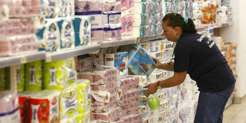 Employee stocking shelves at supermarket grocery with toilet paper