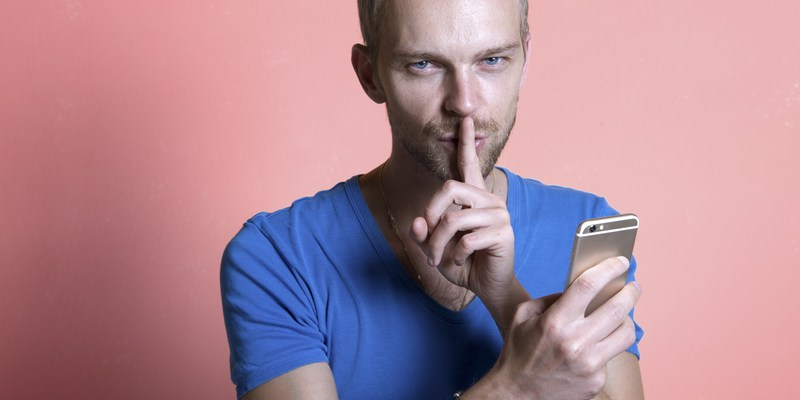 Man making the silence finger with mobile phone in hand