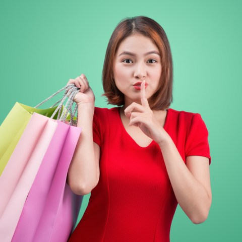 Beautiful young asian woman with colored shopping bags over green