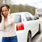 woman with broken car on side of road via dreamstime