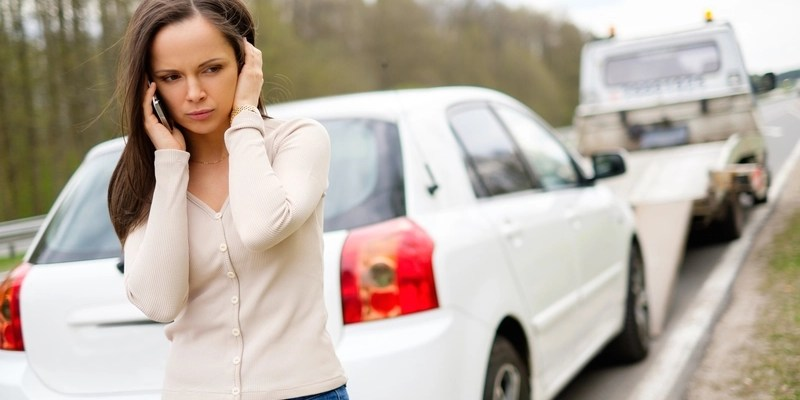 woman with broken car on side of road via dreamstime