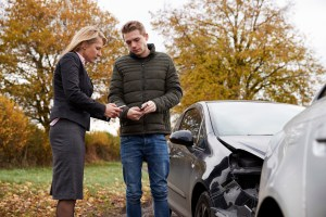 Two Drivers Exchanging Insurance Details After Car Accident