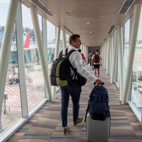 Man boarding plane with carry-on bags