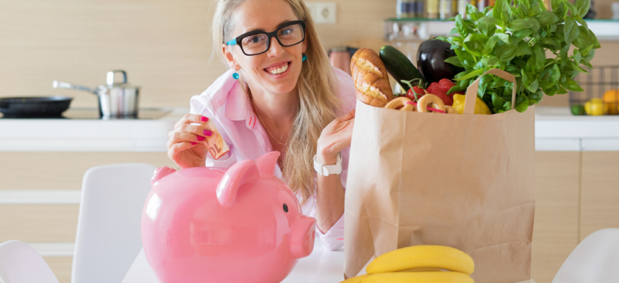 Woman with groceries saving money in piggy bank