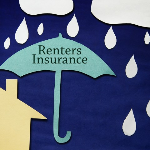 renters insurance written on umbrella in front of house