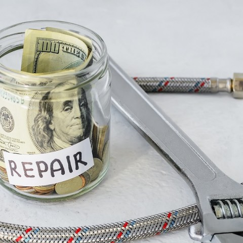 Money in a jar saved for emergency home repair