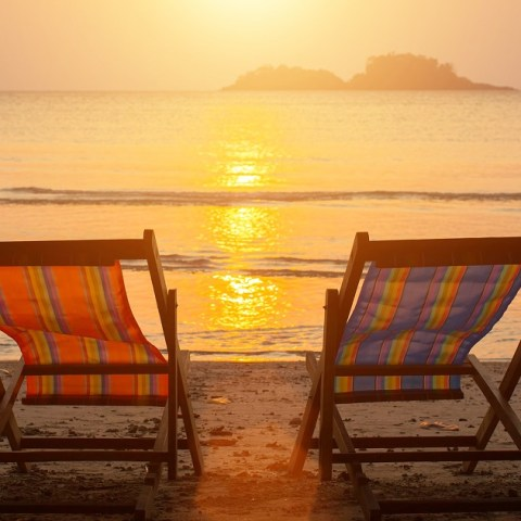 Two chairs on the beach at sunset