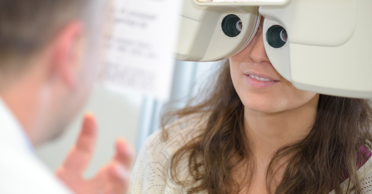 Patient looking through a phoropter during an eye exam