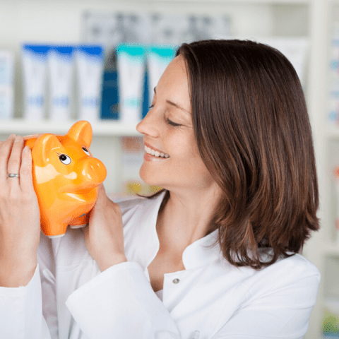 Pharmacist Looking At Piggybank In Pharmacy