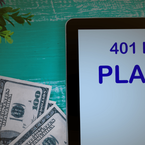 401 K plan in tablet with money on a table