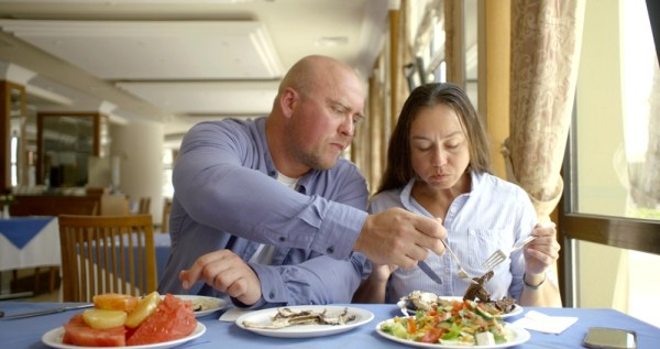 Couple eating food together after grocery shopping.