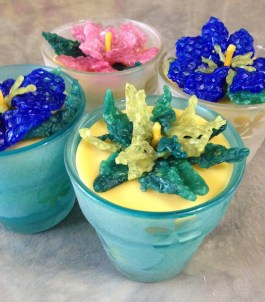 Colorful beeswax votives topped with beeswax flowers. Photo credit: Monika Spykerman