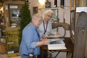 Two Rivers Heritage Museum Karen Johnson and Gayle Godtilbsen look through one of the many themed photo notebooks. This on on early logging.