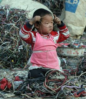 e-waste_child playing with electronic cords and connections in garbage dump