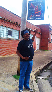 Lucious Spiller under his sign in Clarksdale's historic downtown Arts & Culture District.