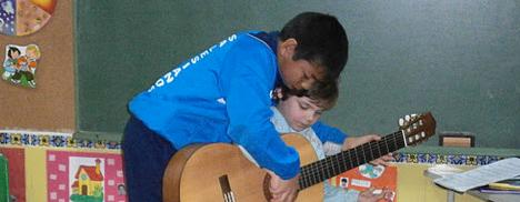 Miguel enseña guitarra a los más peques
