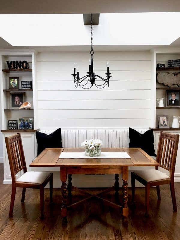 black and white banquette with antique table