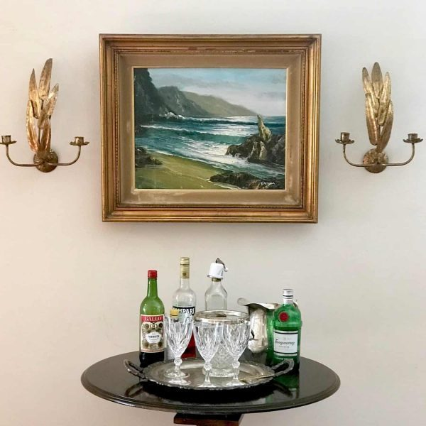 bar table with vintage sconces and oil painting