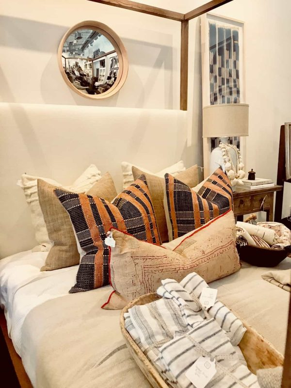 ethnic textile pillows on four poster bed