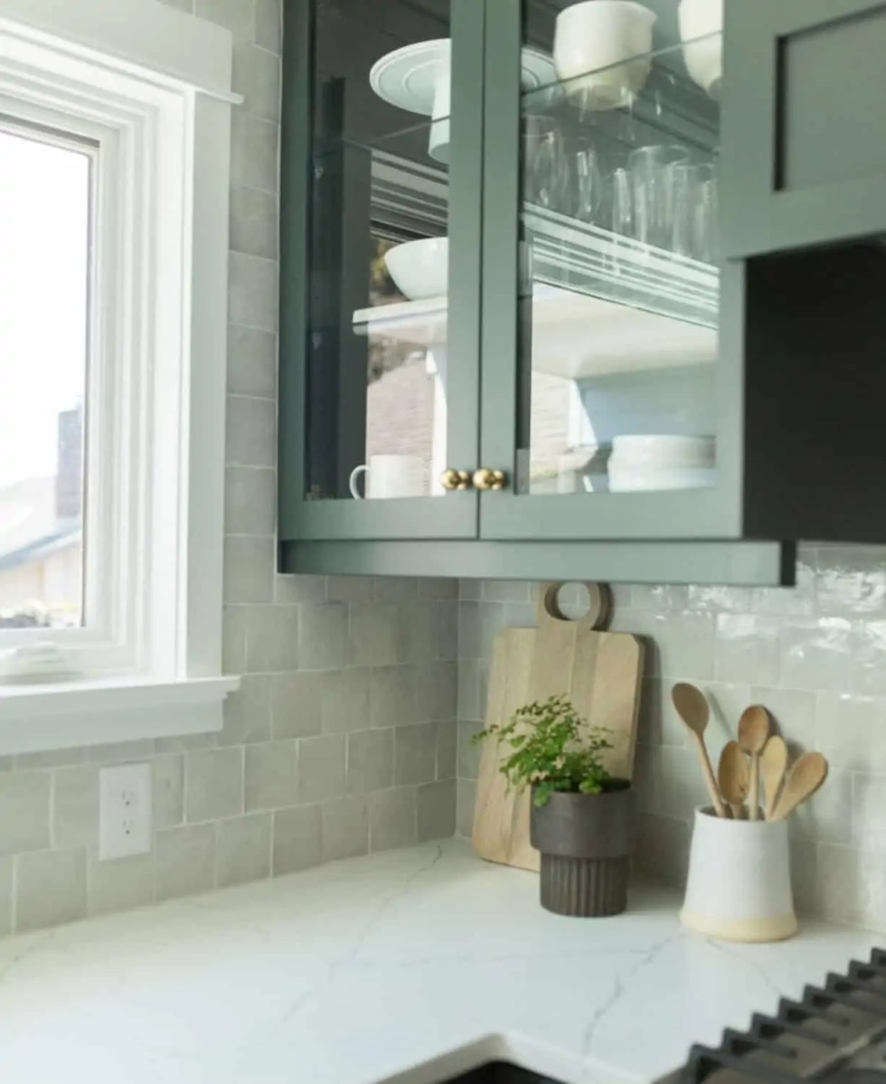 green cabinet with glass front and hand fired tiles