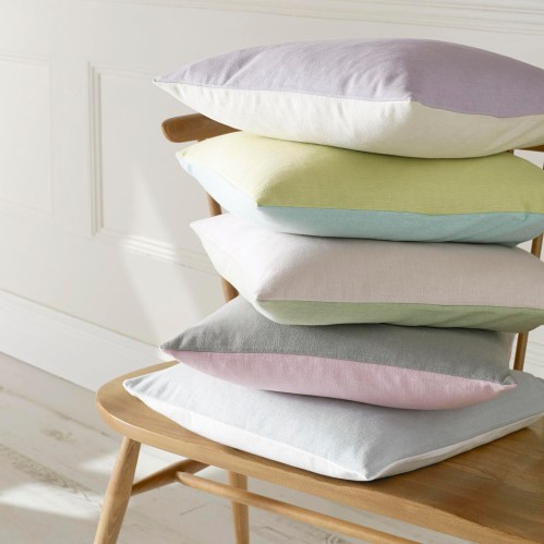 "alt=""photo of pastel multicoloured cushions made from Ashley Wilde Cole Fabric, photo courtesy of Ashley Wilde Ltd"""