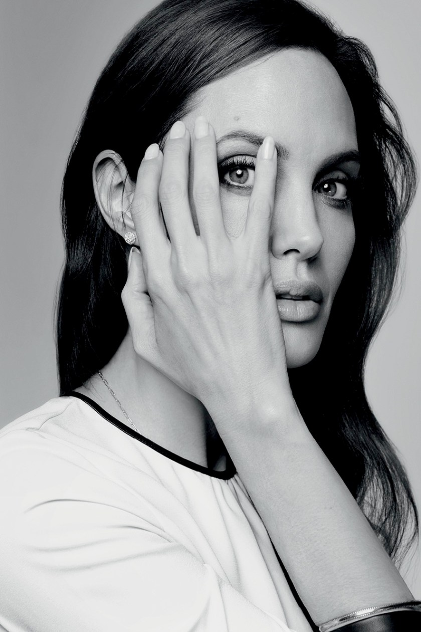 Angelina Jolie with her hand on her face allowing to see her eye through her fingers