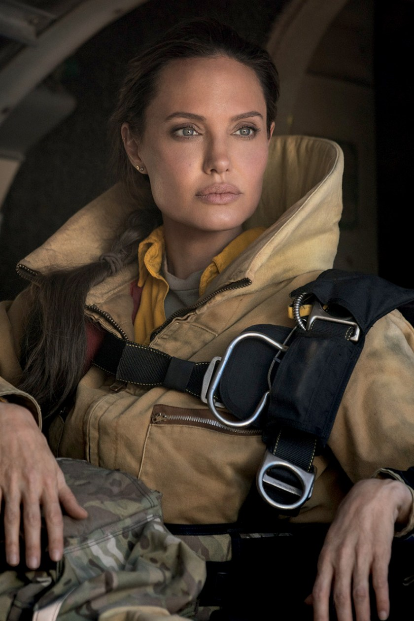 Angelina Jolie looks at the horizon wearing a large coat and wearing seat belt