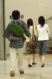 Jeune homme chaussant des «ipponba-geta» (sandale «geta» à une dent centrale) dans le métro de Tokyo