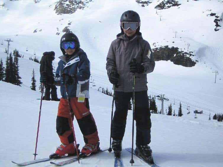 boys posing on ski hill in whistler with kids