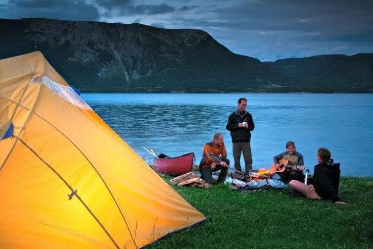 camper in canada sitting by lake strumming guitar