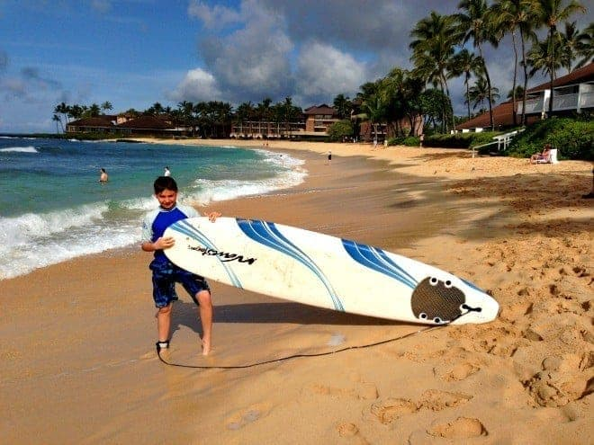 boy holding large surfboard on beach in kauai