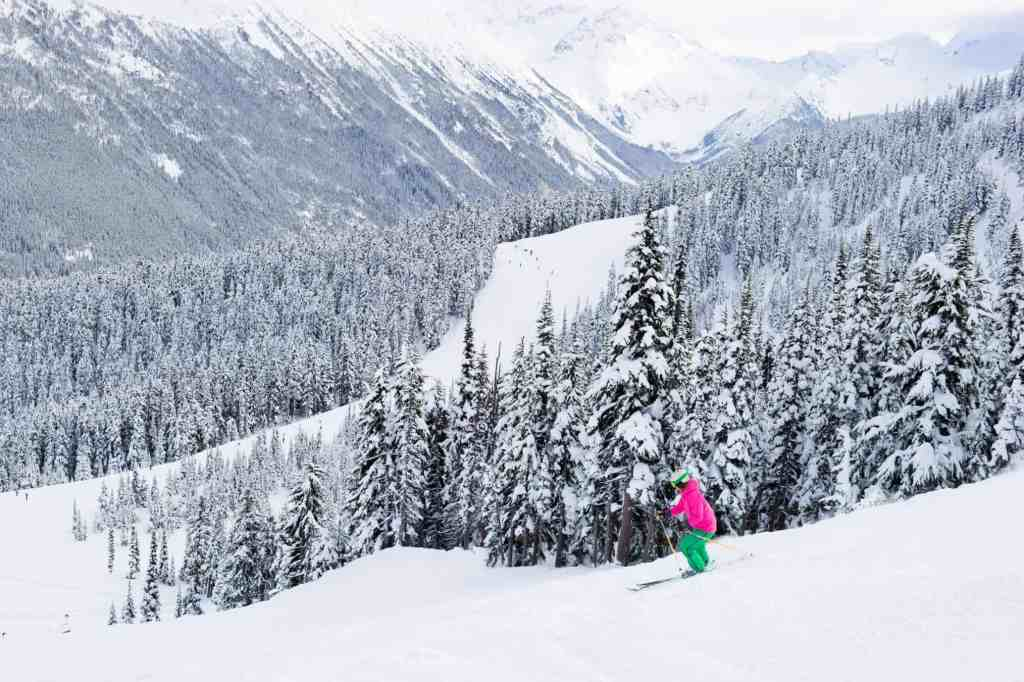 lady skiing down slope in whistler at winter