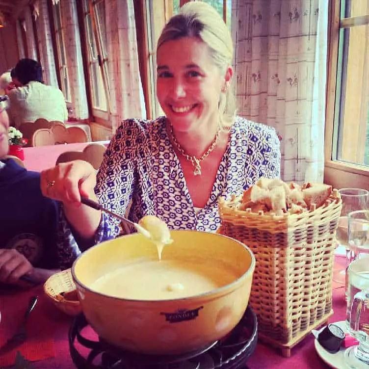 girl dipping bread into cheese fondue