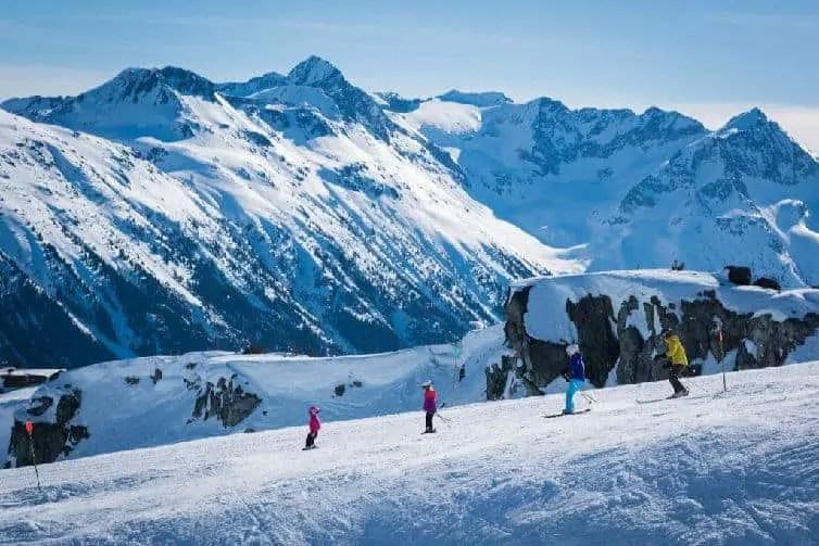 family skiing down slope in winter in whistler