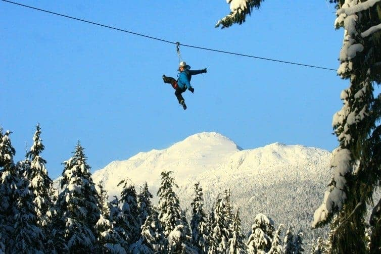person zip lining in winter in whistler