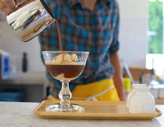 man pouring coffee over ice cream