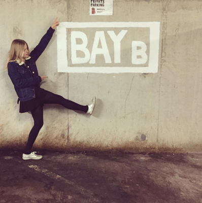 blonde girl baby on the streets in front of a wall