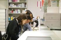 Un'addetta mostra ai visitatori il funzionamento della macchina automatica per il carico dei medicinali.