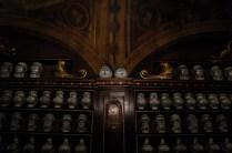 L'antico orologio incastonato tra gli scaffali di legno intagliato, opera dell'ebanista Magistretti.