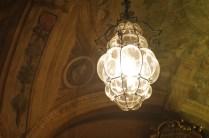 Uno degli splendidi lampadari di vetro soffiato pende dalle volte affrescate.