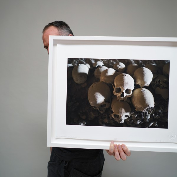 Artist Clayton Porter holding his photograph of a human skull printed with archival pigment ink on rag paper in a white frame.