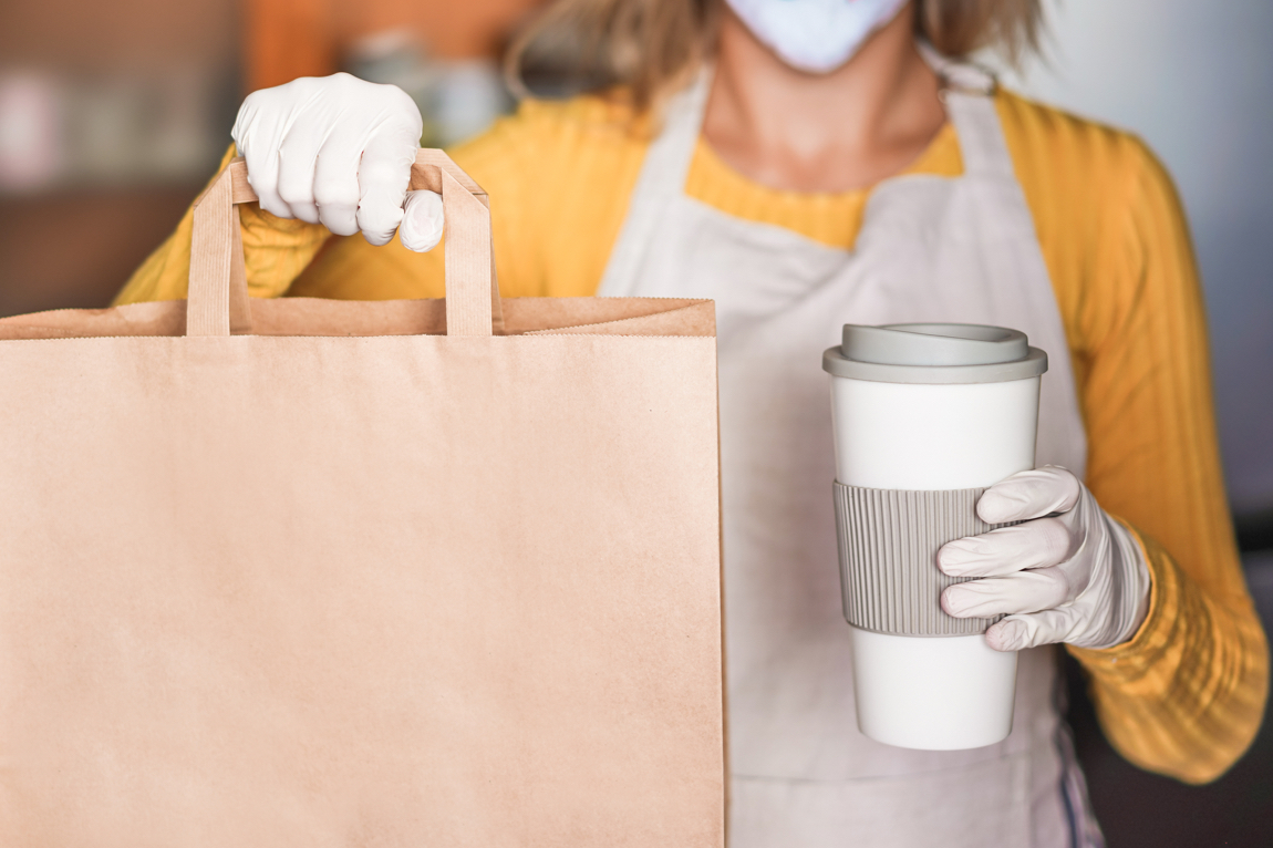 Lady holding paper bag and coffee wearing gloves