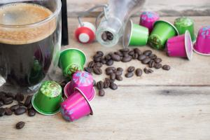 lime green and bright pink nespresso coffee pods with scatterd coffee beans on a table