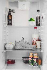 office fridge with shoe on middle shelf guiness beer on top shelf