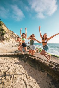4 young women jumping off a rock by the beach