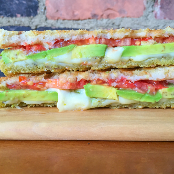 Avocado Cheese Panini - the sandwich which combines creamy avocado, sun-ripened tomatoes, mozzarella cheese, and pesto.