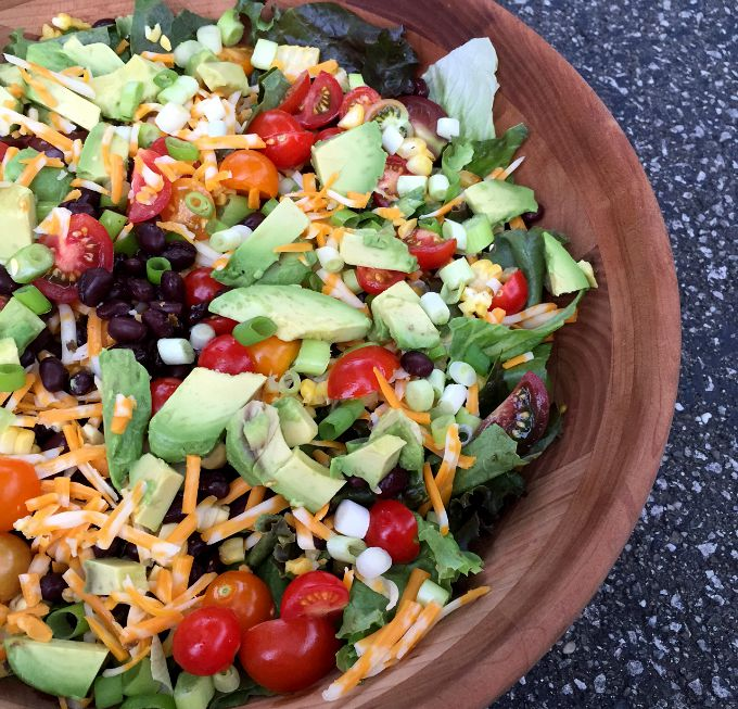This simple and healthy Southwestern Salad combines corn, black beans, avocado, green onions, pepper jack cheese, and cherry tomatoes. The Cilantro Lime Vinaigrette is the icing on the proverbial cake.